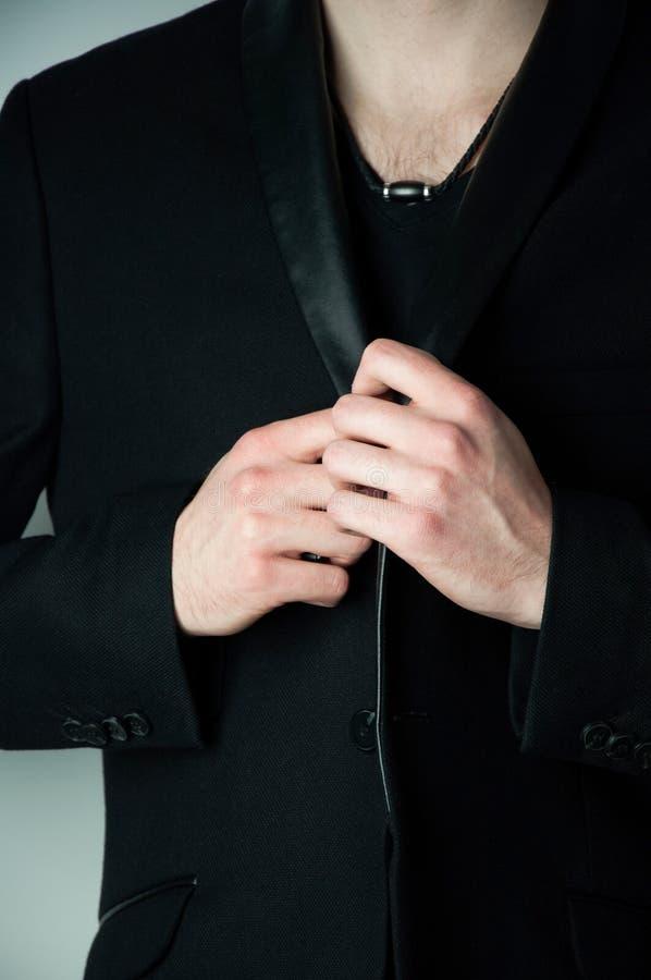Подрезанный главный человек в черной футболке v держа воротник блейзера стоковая фотография rf
