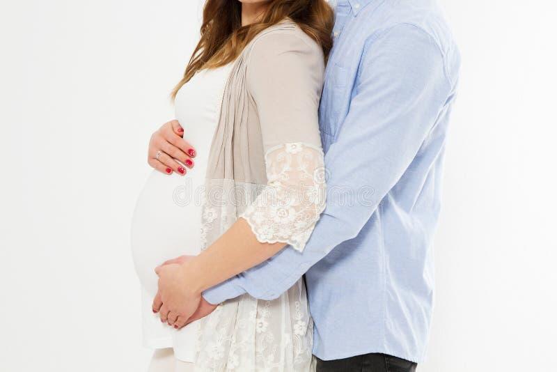 Подрезанный портрет красивой беременной женщины и ее красивого супруга обнимая tummy человек влюбленности поцелуя принципиальной  стоковые изображения