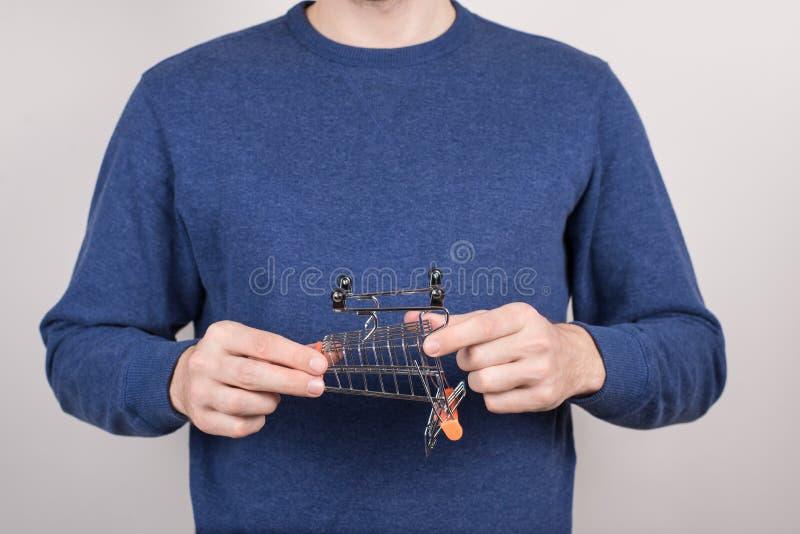 Подрезанный портрет фото крупного плана расстроенного парня держа небольшую маленькую тележку вагонетки вверх ногами изолировал с стоковая фотография rf
