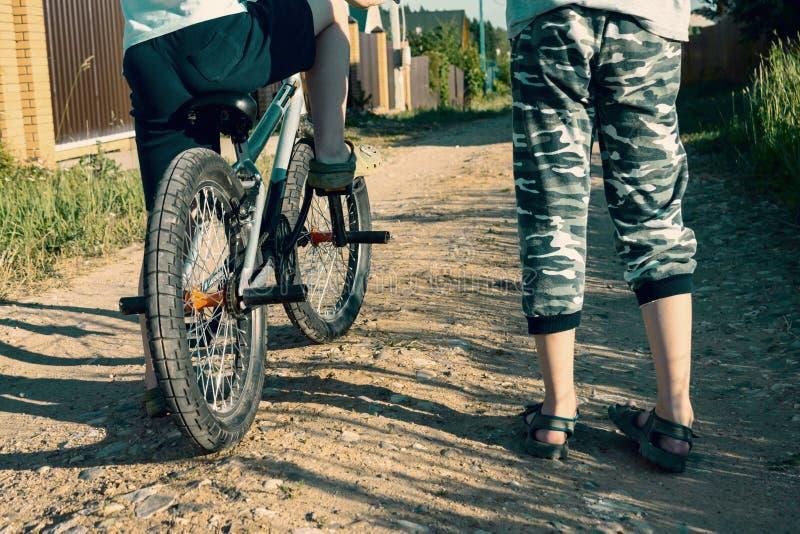2 подрезанных мальчика, друзья с велосипедом на открытом воздухе стоковое фото