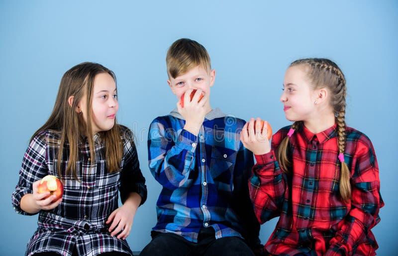 Подростки группы жизнерадостные имея потеху и есть яблоки Здоровое питание dieting и витамина Мальчик и подруги едят стоковое фото