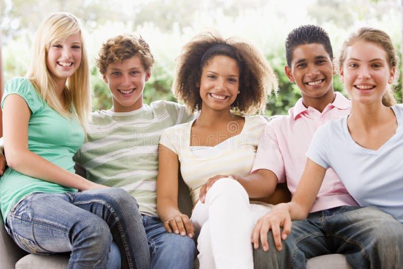 подростки группы кресла сидя стоковая фотография