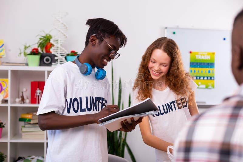 Подростки делая примечания после сортировать немногого в добровольной организации стоковая фотография