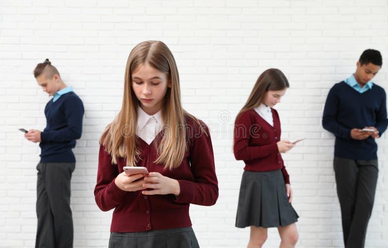 Подростки используя мобильные телефоны на школе Концепция наркомании интернета стоковое фото