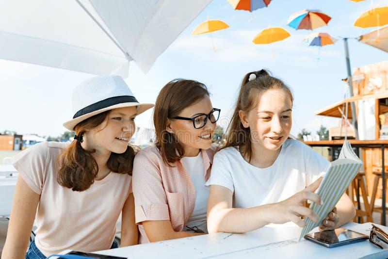 Подростки мамы и дочерей имеют потеху, говорить, взгляд и прочитанную смешную книгу Сообщение родителя и детей подростков стоковая фотография rf