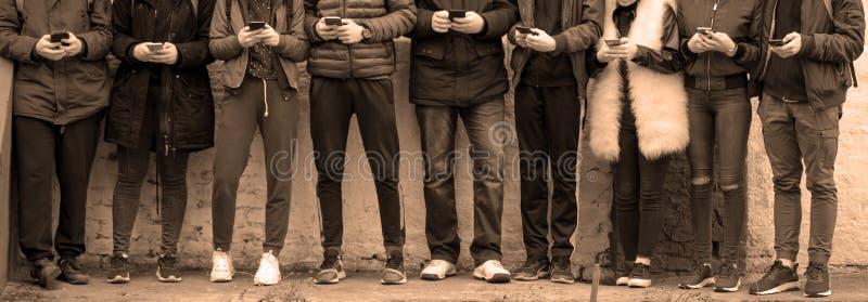 Подростки с телефонами против стены стоковая фотография rf