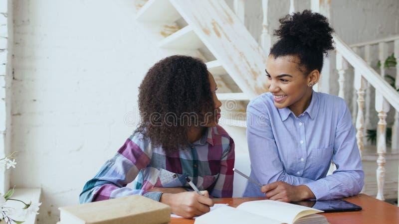 Подростковая курчавая с волосами маленькая девочка смешанной гонки сидя на сфокусированный концентрировать таблицы учащ уроки и е стоковое изображение rf