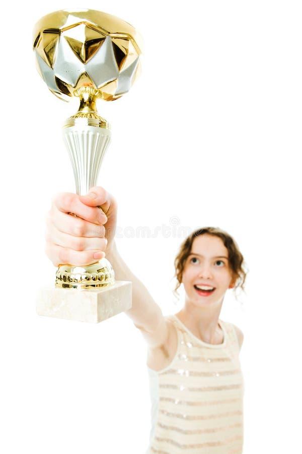 Подросткового возраста женская девушка чемпиона поднимает вверх выигрывая чашка стоковые изображения