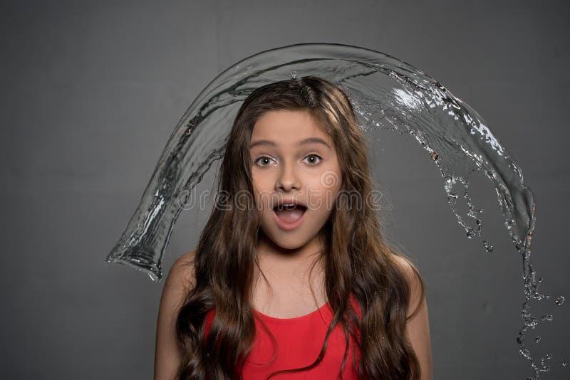 Подросткового возраста удивленная девушка и вода лить над ей стоковые фото
