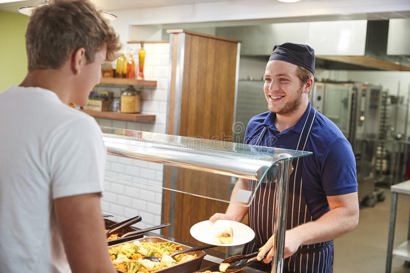 Подростковые студенты будучи послуженным еда в буфете школы стоковое изображение