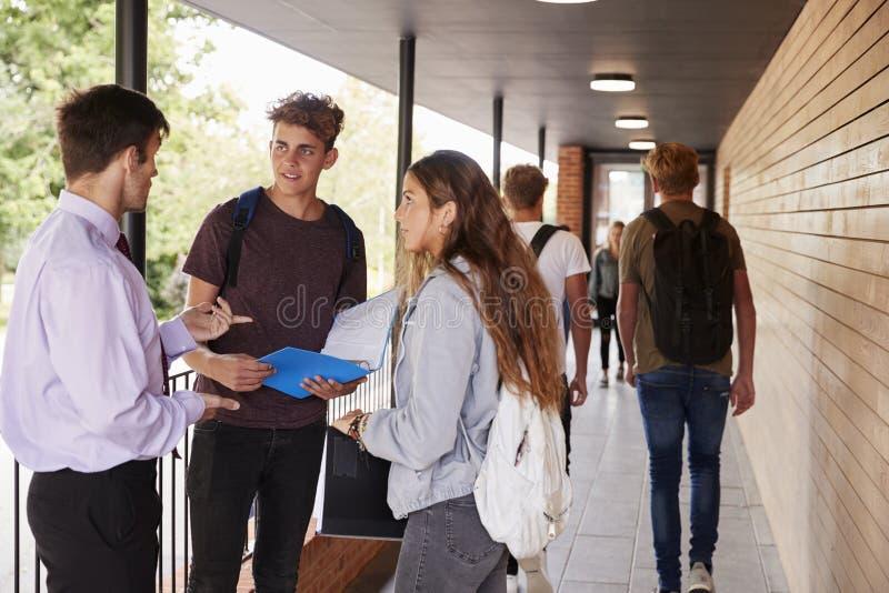 Подростковые студенты говоря к учителю вне школьных зданий стоковая фотография rf