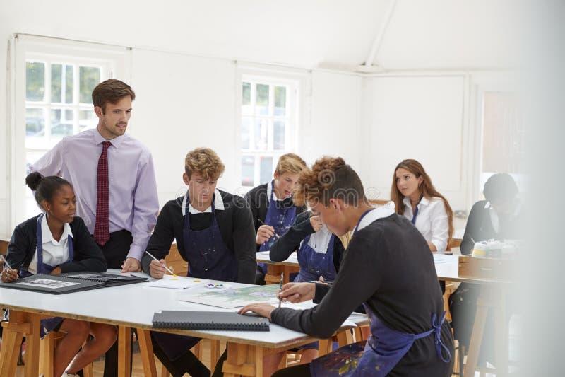 Подростковые студенты слушая к учителю в художественном классе стоковые изображения