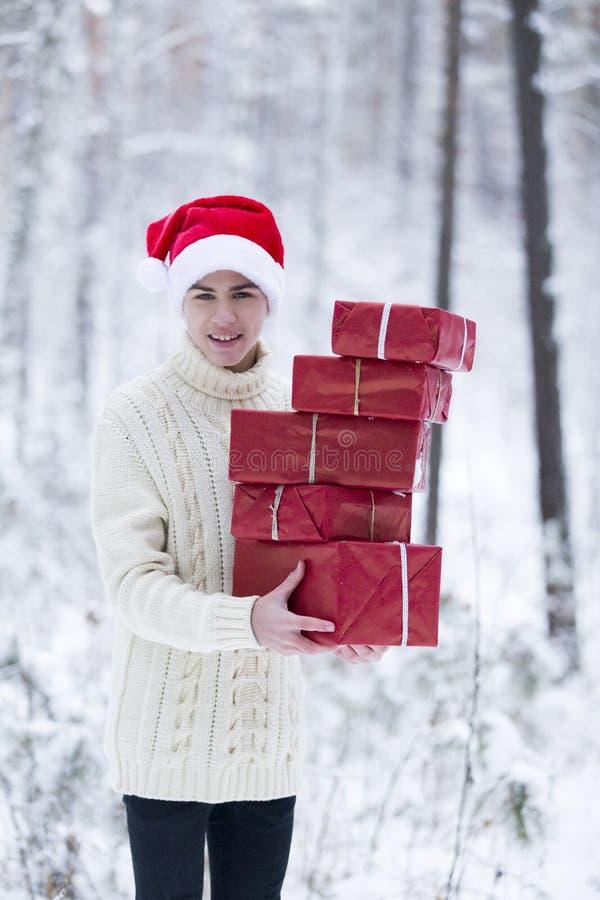 Подросток в шляпе Санта Клаусе собирает подарки в снежном лесе внутри стоковое фото