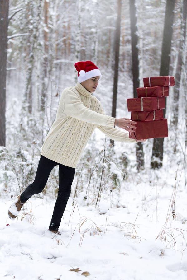 Подросток в шляпе Санта Клаусе собирает подарки в снежном лесе внутри стоковая фотография