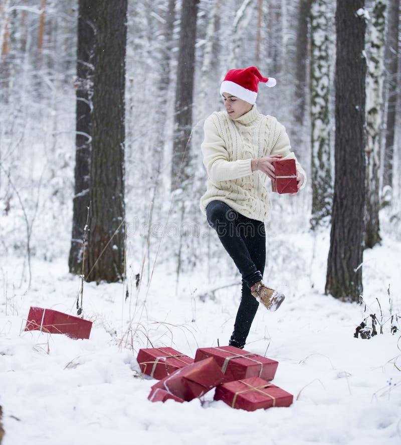 Подросток в шляпе Санта Клаусе собирает подарки в снежном лесе внутри стоковая фотография rf