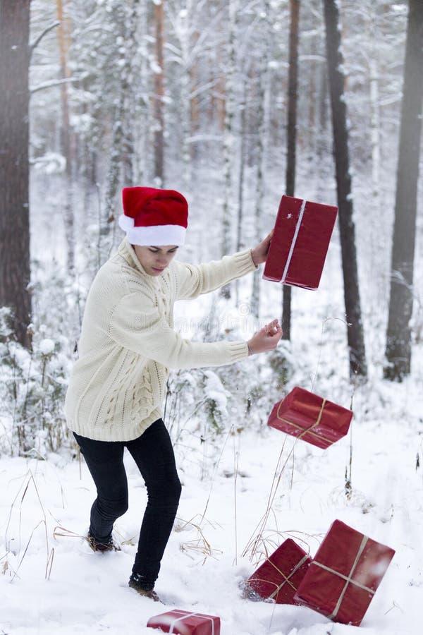 Подросток в шляпе Санта Клаусе собирает подарки в снежном лесе внутри стоковое изображение