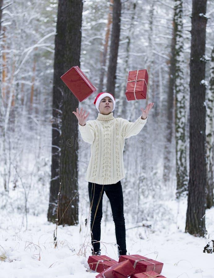 Подросток в шляпе Санта Клаусе собирает подарки в снежном лесе внутри стоковые изображения