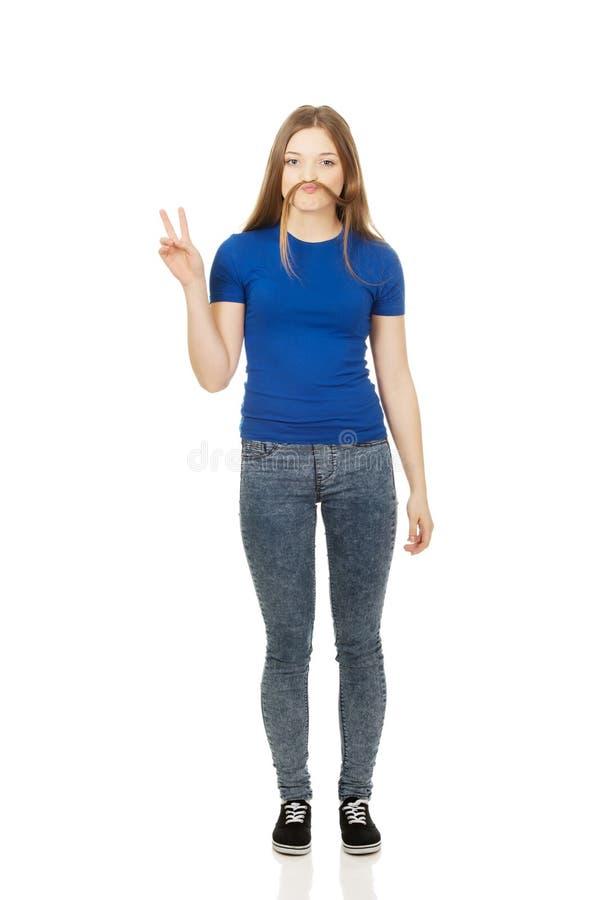 Подросток делая усик от волос стоковое изображение