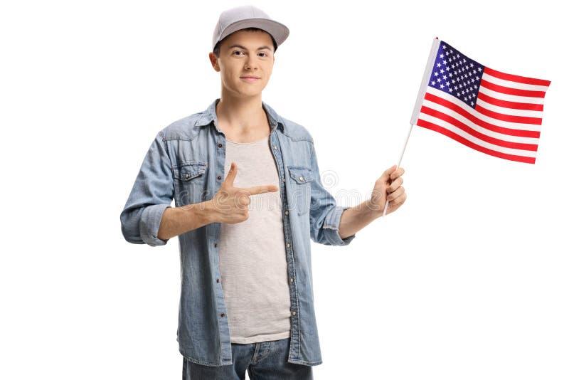 Подросток держа американский флаг и указывать стоковое изображение rf