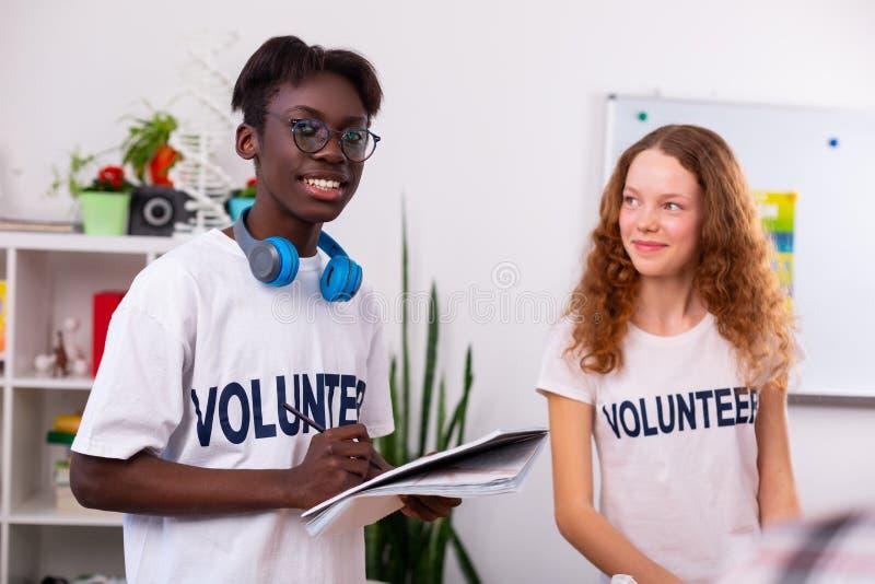 Подросток держа бумагу и ручку после сортировать сор с другом стоковые фотографии rf