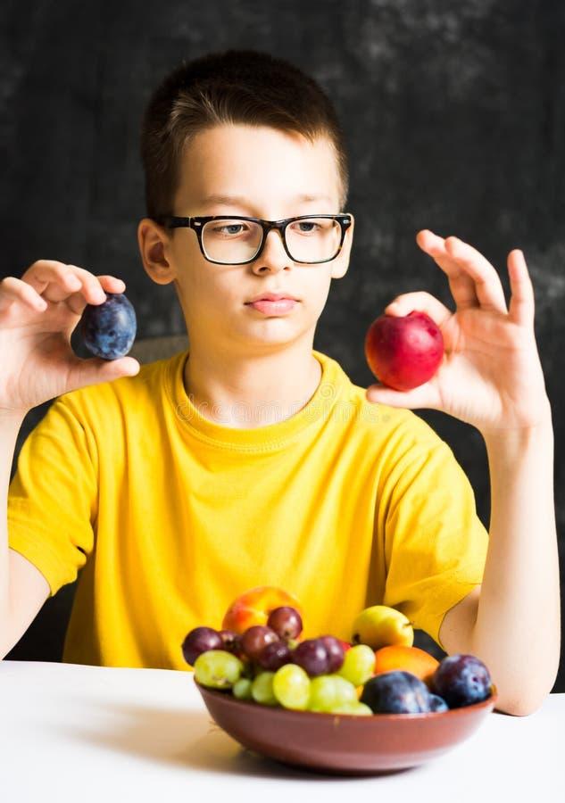 Подросток есть плодоовощ для его закуски стоковые фотографии rf