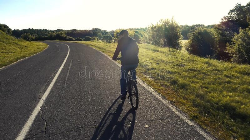 Подросток ехать велосипед на лете дороги sunlit стоковая фотография