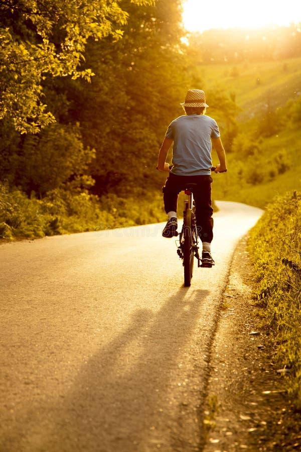 Подросток ехать велосипед на лете дороги sunlit стоковые фотографии rf