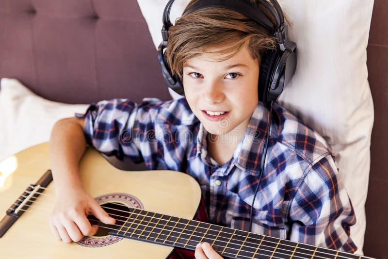 Подросток играя акустическую гитару в кровати стоковые изображения