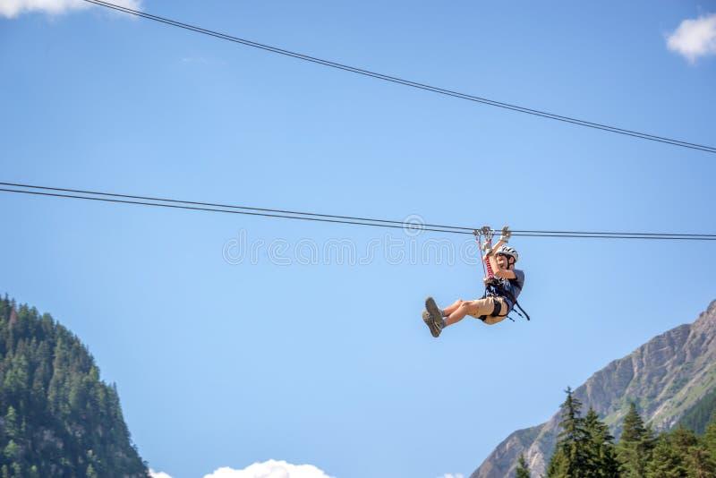 Подросток имея потеху на линии в Альпах, приключении застежка-молнии, взбираясь, через ferrata во время каникул в лете стоковые фото