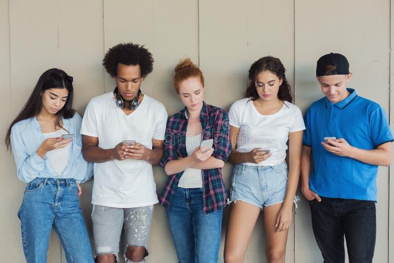 Подросток используя мобильные телефоны, незаинтересованные друг к другу стоковые изображения
