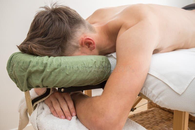 Подросток кладя на таблицу массажа стоковое изображение