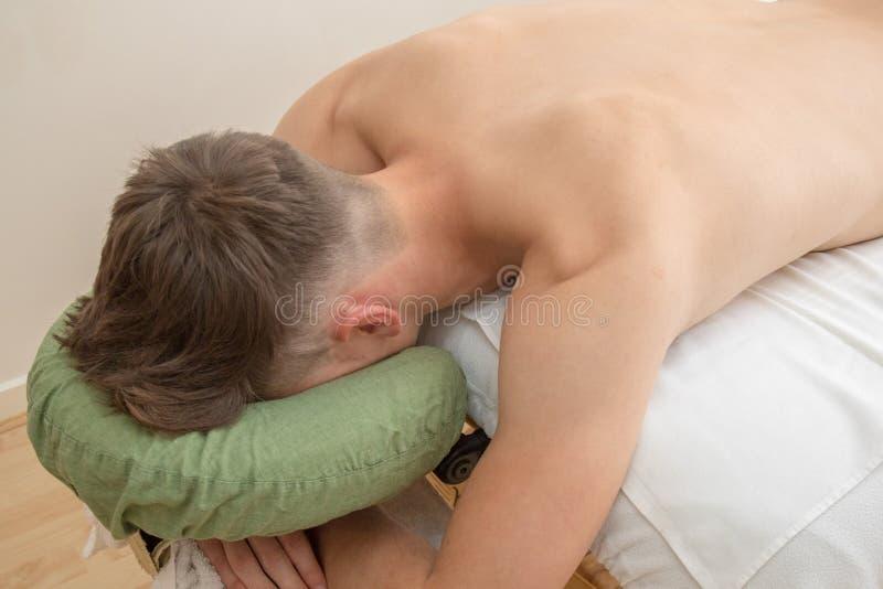 Подросток кладя на таблицу массажа стоковое изображение rf