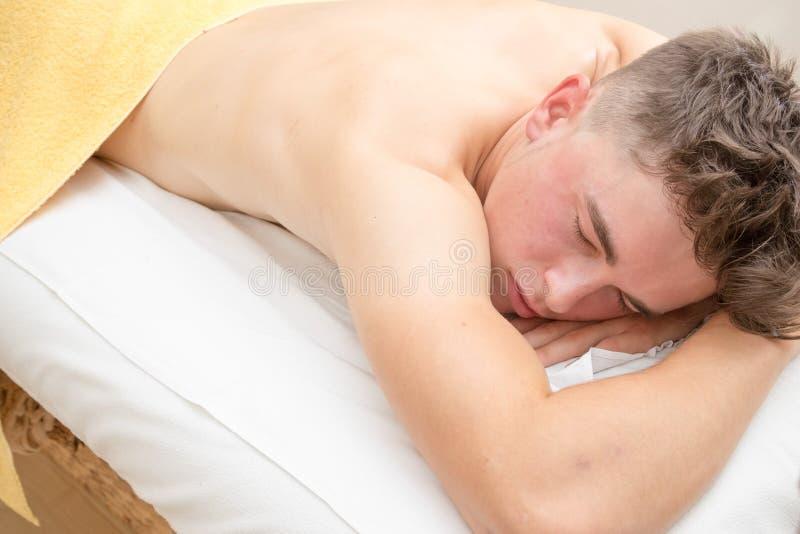 Подросток кладя на таблицу массажа стоковая фотография