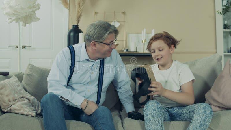 Подросток показывает очки для своего дедушки стоковые изображения