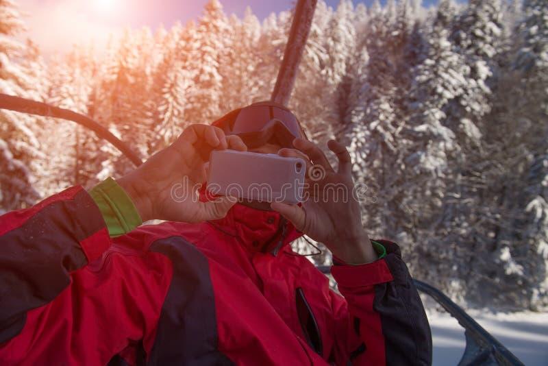 Подросток принимая фото со смартфоном от подъема лыжи в горы зимы стоковые изображения rf