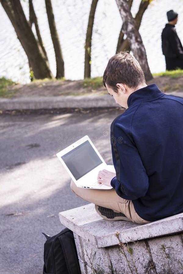 Подросток работает за компьтер-книжкой стоковое фото