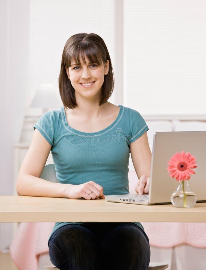 подросток счастливой компьтер-книжки стола сидя стоковое фото rf