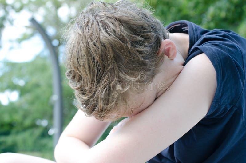 Подросток с головой в оружиях стоковая фотография rf