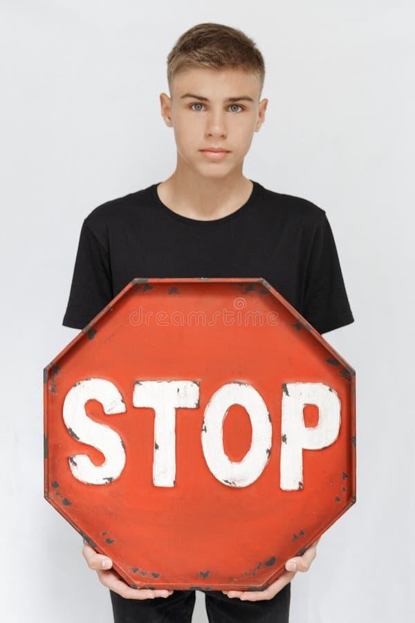 Подросток с символом стопа, останавливает, на белой предпосылке в a стоковая фотография