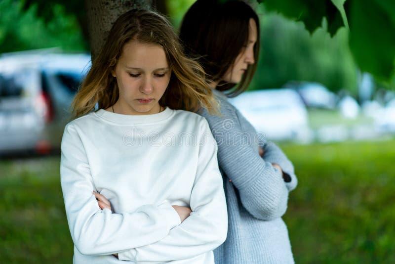 Подросток школьницы 2 девушек, в лете в парке деревом Концепция ссоры, проблем, возмущения, недовольства стоковая фотография