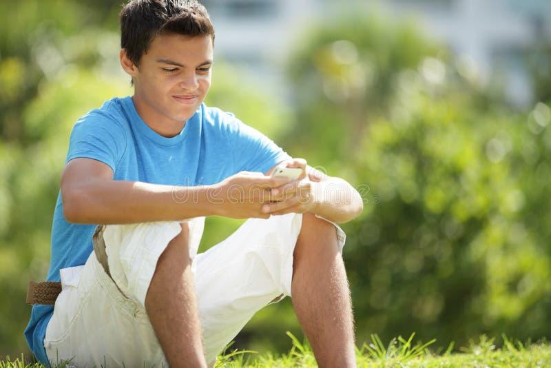 Подросток texting на телефоне стоковая фотография rf