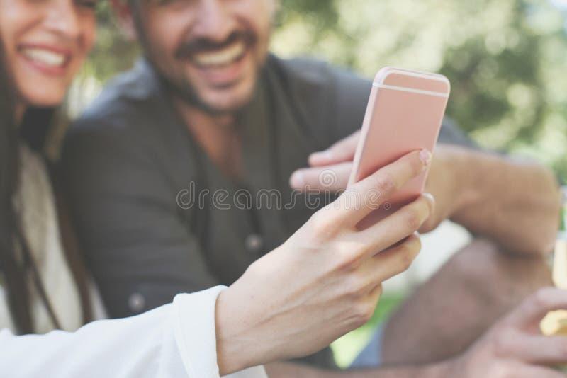 Подруга показывая что-то смешное на умном телефоне стоковые фото