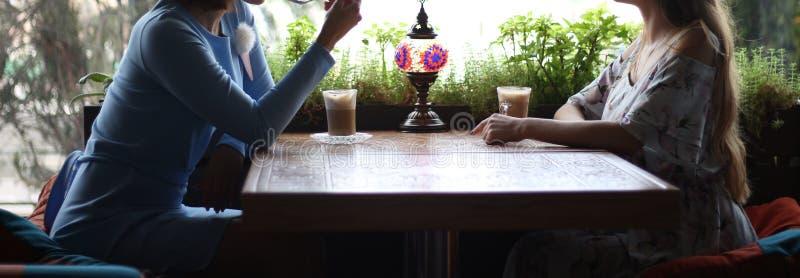 Подруги наслаждаясь в кафе совместно Молодые женщины встречая в кафе встречать 2 женщин в кафе для кофе голубое платье, платье вн стоковое фото