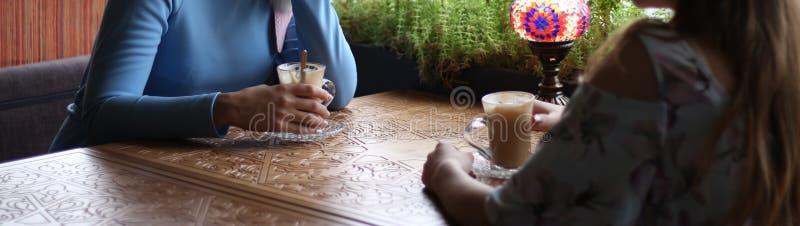 Подруги наслаждаясь в кафе совместно Молодые женщины встречая в кафе встречать 2 женщин в кафе для кофе голубое платье, платье вн стоковые изображения