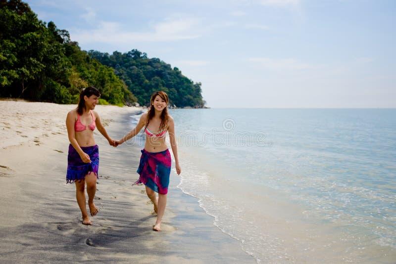 подруги пляжа гуляя стоковая фотография