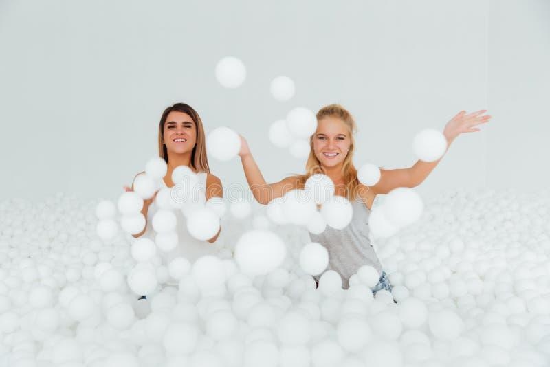 Подруги портрета счастливые стоят окруженными белыми пластичными шариками в сухом бассейне стоковые изображения rf