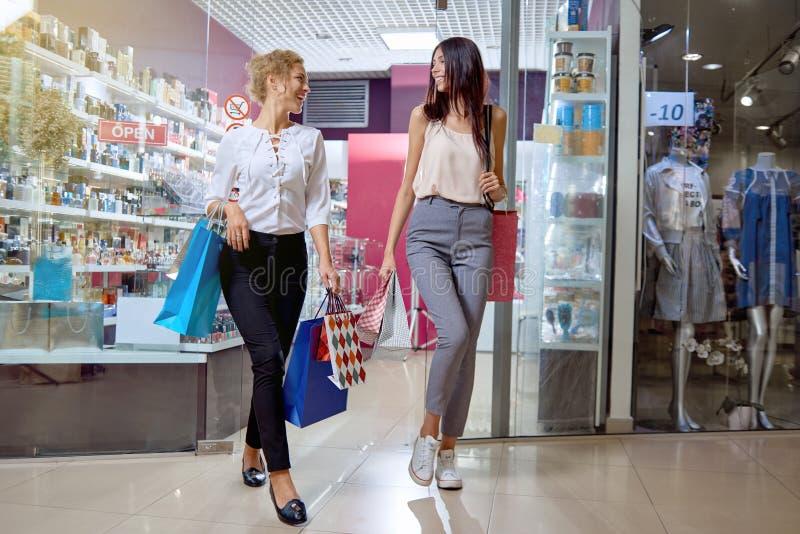 2 подруги приходя вне от магазина косметик стоковое изображение rf