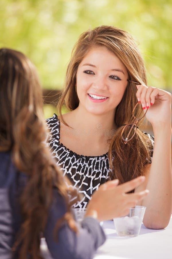 2 подруги смешанных гонки предназначенных для подростков говоря над пить Outdoors стоковое изображение