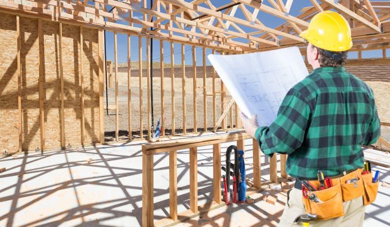 Подрядчик с трудной шляпой и планы стоя в строительной площадке стоковое изображение rf