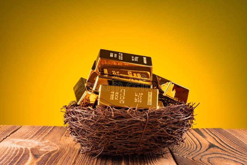 Подсвеченное золото в слитках на концепции гнезда смотреть после вашего вклада стоковая фотография rf